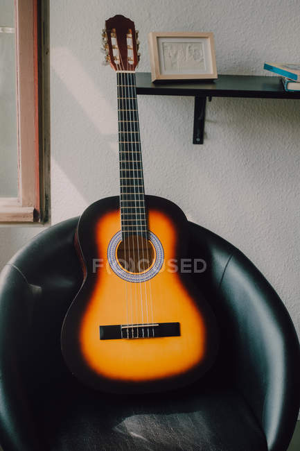 Modern acoustic guitar on minimalist on round chair by white wall with shelf at home — Stock Photo