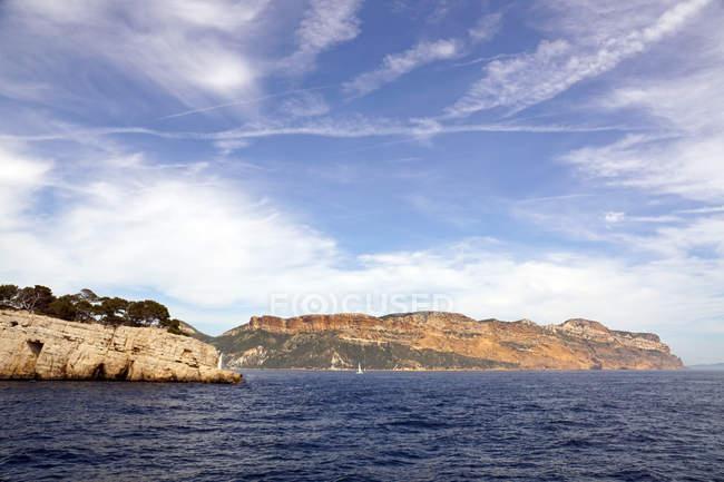 Voilier blanc en mer et rochers magnifiques — Photo de stock
