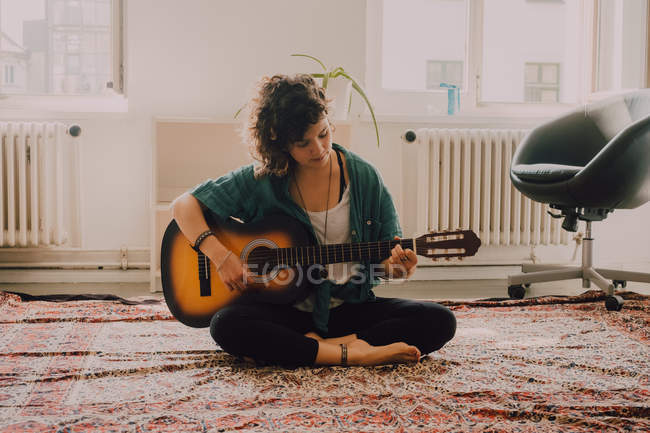 Relaxed woman in casual clothes playing acoustic guitar while sitting on floor in minimalistic room — Stock Photo