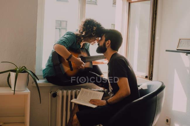 Mujer feliz tocando la guitarra y sentado en el alféizar de la ventana y besar hombre sosteniendo libro - foto de stock