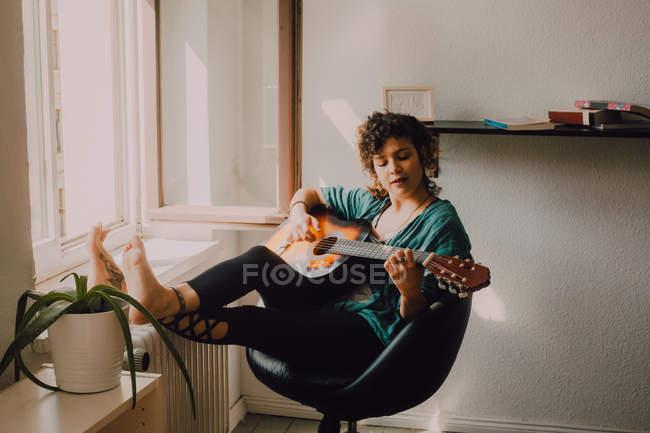 Entspannte barfüßige Frau in lässiger Kleidung spielt Akustikgitarre, während sie zu Hause auf einem Stuhl neben dem Fenster sitzt — Stockfoto