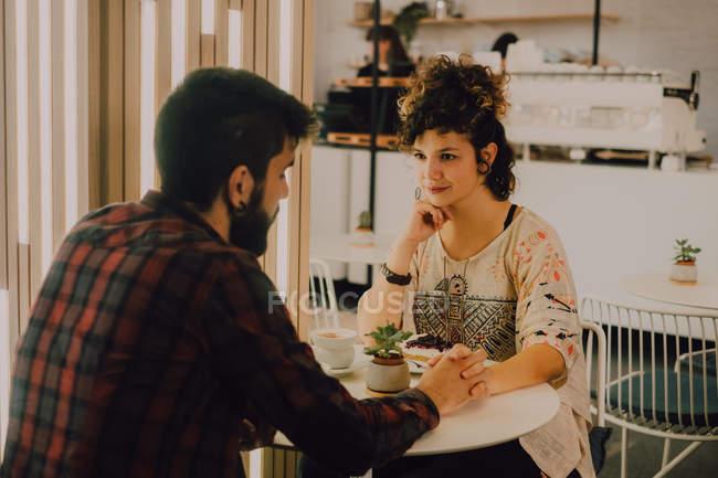 Zärtliches Paar in lässiger Kleidung hält Händchen, während es am Tisch im Café sitzt und einander anschaut — Stockfoto