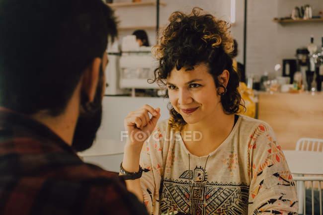 Zärtliches Paar in lässiger Kleidung sitzt am Tisch im Café und schaut sich an — Stockfoto