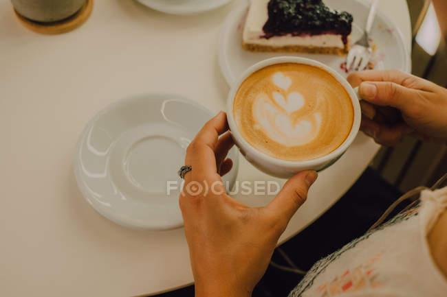 Вид от первого лица женщины, держащей кружку, сидя в современной кофейне — стоковое фото