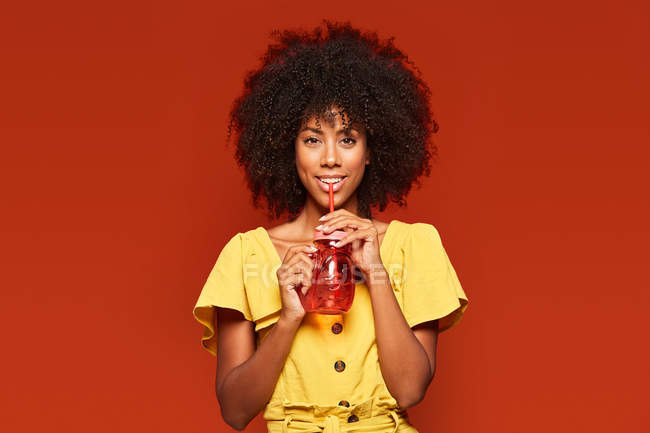 Dreamy African American woman holding red jar with straw and enjoying beverage on red background looking at camera — Stock Photo