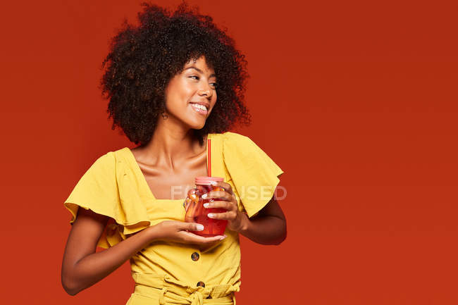 Cheerful African American woman with curly hair holding red jar with straw and enjoying beverage on red background — Stock Photo