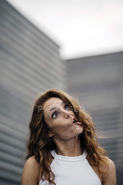 Радісна жінка з рудим волоссям висміює очі й губи, а на сивому фоні гризе фотоапарат. — стокове фото