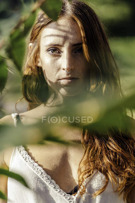 Red haired freckled confidently standing and looking at camera through leaves in forest — Stock Photo