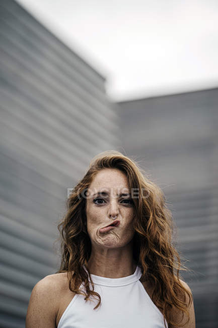 Red haired joyful woman making funny expression with eyes and lips and grimacing at camera on grey background — стокове фото