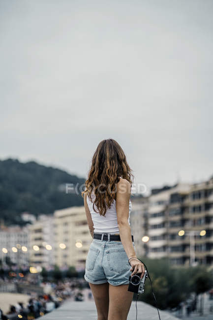 Back view of woman in shorts with camera in hands looking at evening view of city lights and buildings in street — Foto stock