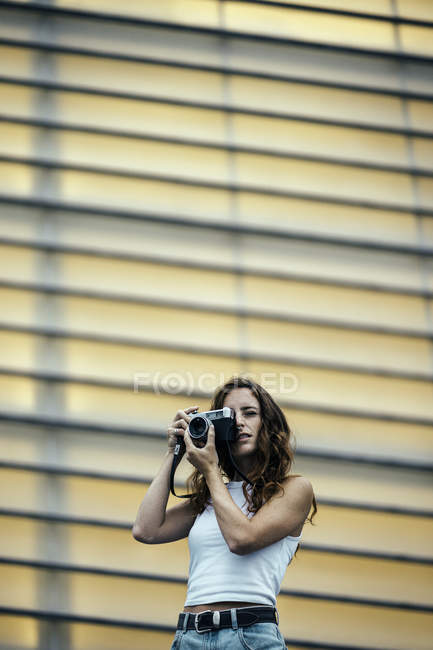 Stylish woman with red hair adjusting photo camera in hand and looking through viewfinder, modern building on the background — Stock Photo