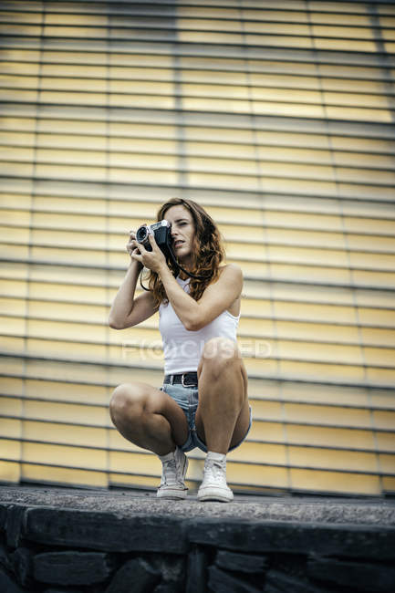 Stylish woman with red hair adjusting photo camera in hand and looking through viewfinder while crouching down — Stock Photo