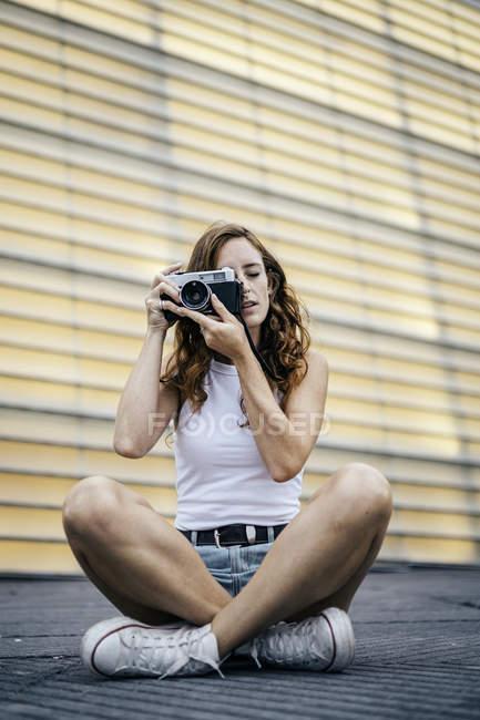 Elegante donna con i capelli rossi regolazione fotocamera fotografica in mano e guardando attraverso mirino mentre si siede — Foto stock