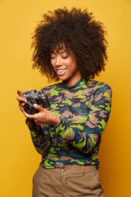 Афроамериканский фотограф пересматривает снимки на стильную фотокамеру, стоя на желтом фоне — стоковое фото