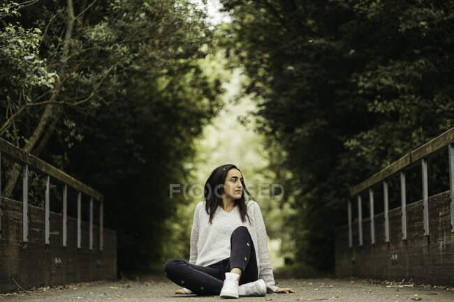 Mulher encantadora livre em suéter confortável sentado na estrada vazia no beco verde — Fotografia de Stock