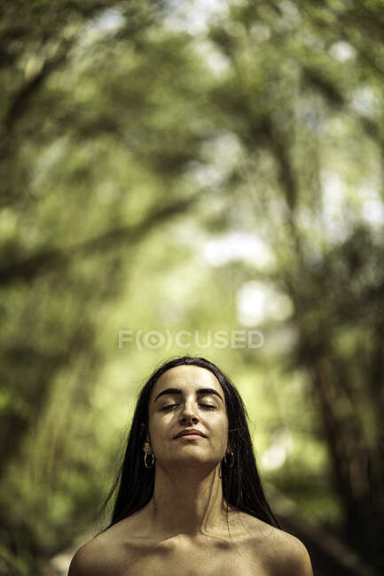 Charming tranquil woman with naked torso and closed eyes thinking in green park — Stock Photo