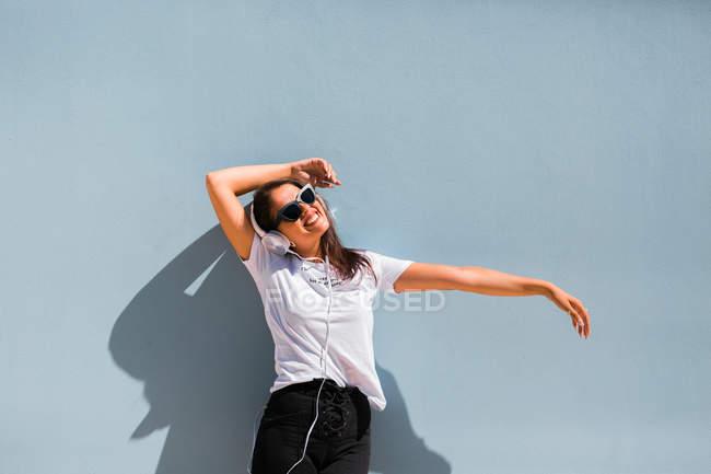 Belle femme en tenue décontractée et écouteurs sur le cou debout avec les mains à côté du mur bleu du bâtiment sur la rue de la ville — Photo de stock