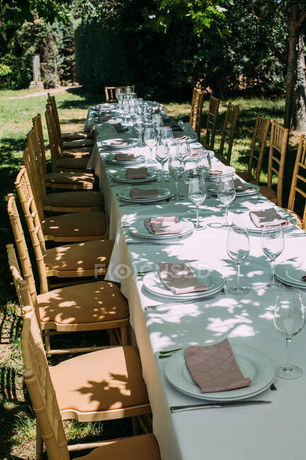 Outdoor rustic celebration table with cutlery and glasses — Stock Photo