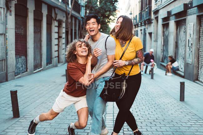 Sorridenti persone multietniche in abiti casual che giocano mentre passeggiano lungo la strada urbana — Foto stock