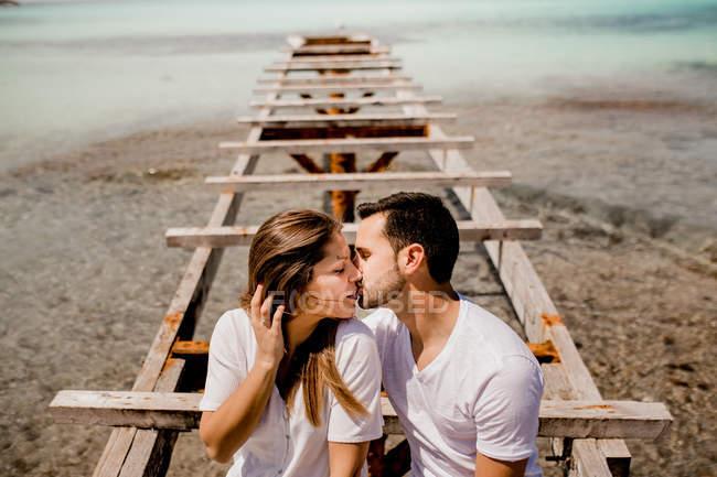 Счастливые влюбленные сидят на разрушенном пирсе на берегу моря — стоковое фото
