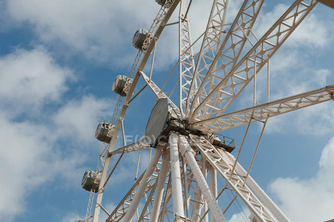 Low angle of modern observation wheel at funfair and blue cloudy sky on background — Stock Photo