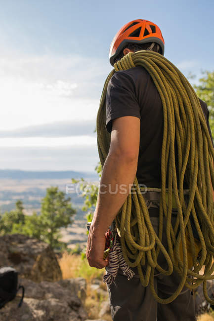 Back view of climber prepares his equipment to start climbing - foto de stock
