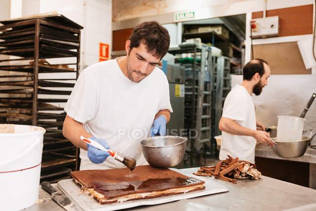 Концентрированный кондитер, намазывающий шоколад сверху на вкусный торт, стоя возле стола в пекарне — стоковое фото