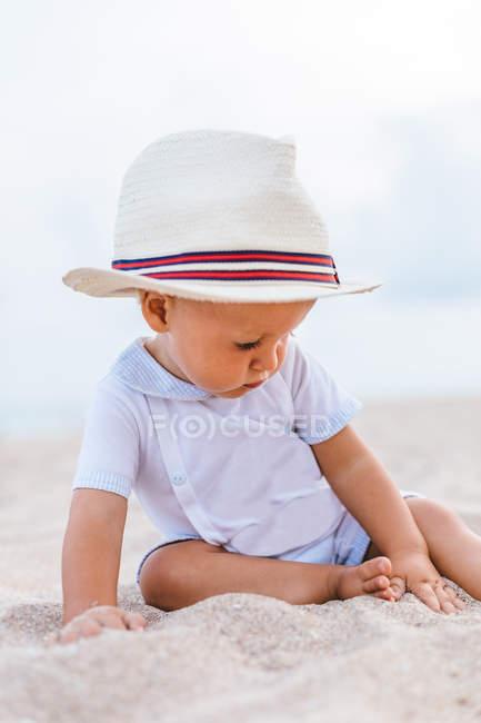 Vista frontale di un bambino sulla spiaggia con un cappello — Foto stock