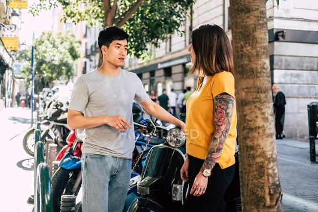 Современные трезвенные многонациональные люди, разговаривающие, стоя возле мотоцикла на солнечной тротуаре — стоковое фото