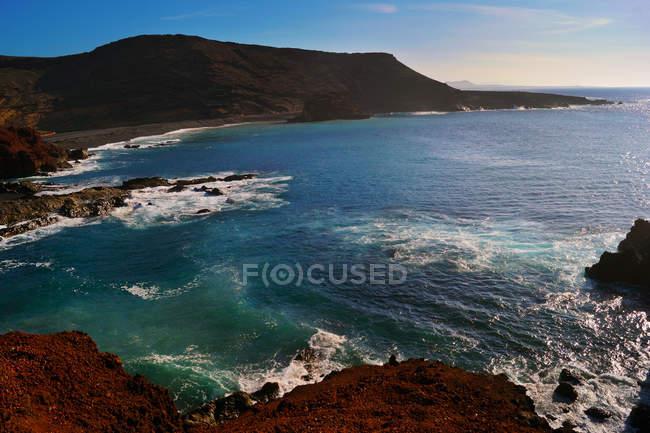Bella e pittoresca vista della superficie dell'acqua di mare tra alte scogliere rocciose nella giornata di sole — Foto stock