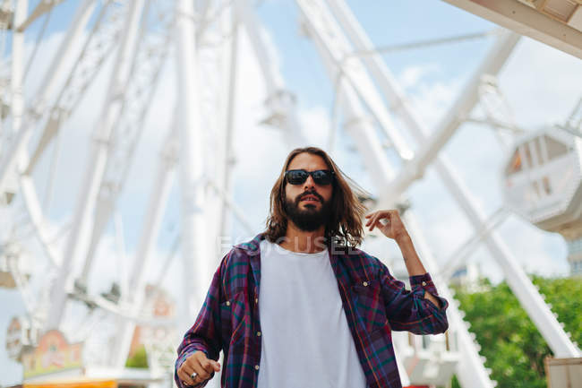 Bearded man in sunglasses standing by modern observation wheel on sunny day — Stock Photo