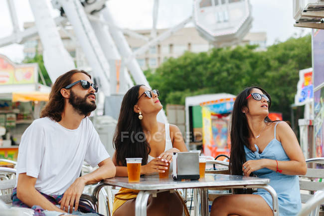 Persone rilassate in occhiali da sole che reggono tazze usa e getta di birra e tifo mentre riposano a tavola accanto alla ruota panoramica — Foto stock