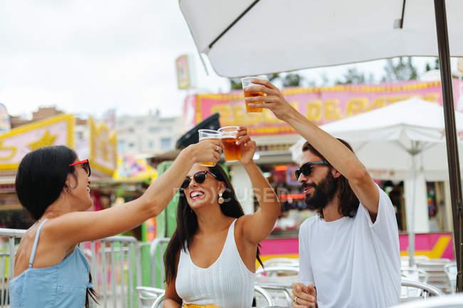 Personas relajadas en gafas de sol sosteniendo vasos de cerveza desechables y animando mientras descansan en la mesa junto a la rueda de la fortuna - foto de stock