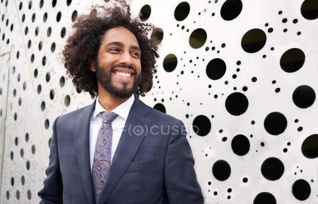 Empreendedor americano africano alegre que está ao lado da parede holey — Fotografia de Stock