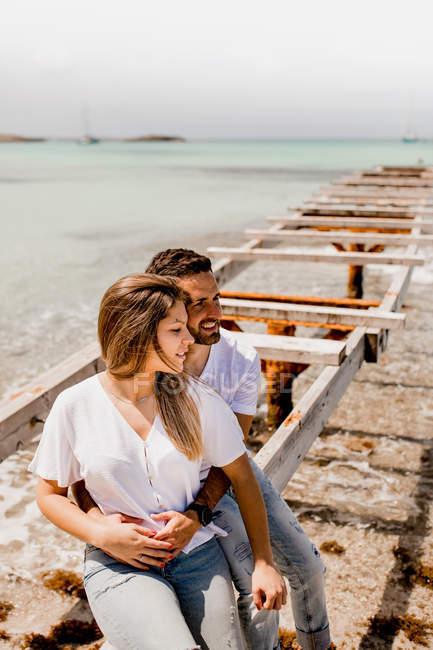 Verliebte sitzen auf zerstörter Seebrücke am Meeresufer — Stockfoto