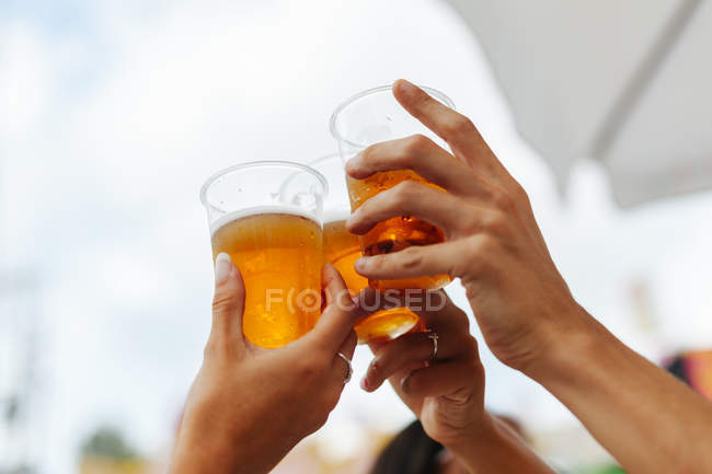 Cropped image of friends holding disposable cups of beer and cheering while resting at table beside Ferris wheel — стокове фото