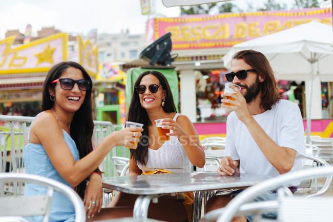 Розслаблені люди в сонцезахисних окулярах, що тримають одноразові чашки пива і веселяться, відпочиваючи за столом біля керма Ферріса. — стокове фото