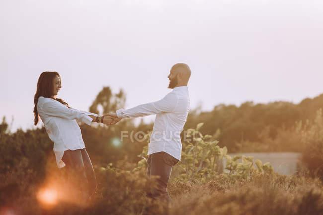 Вид сбоку счастливой влюбленной пары в повседневной одежде, держащейся за руки и смотрящей друг на друга, стоя на поле — стоковое фото