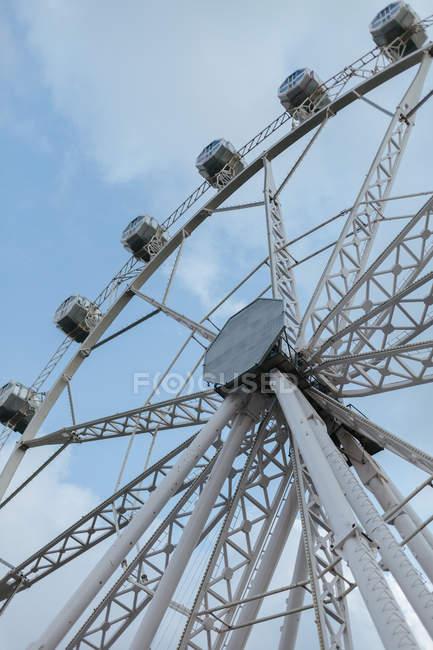 Angle bas de la section de roue d'observation moderne au parc d'attractions et ciel bleu — Photo de stock
