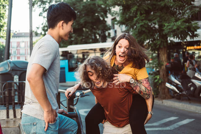 Playful multiethnic people laughing and riding piggyback while standing on sunny city street — стокове фото