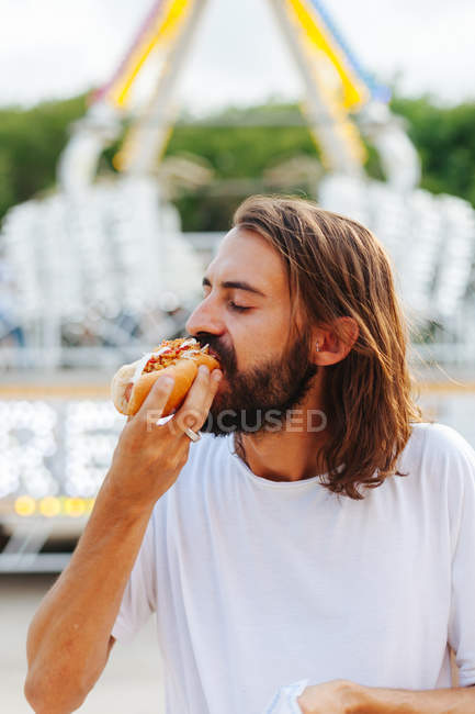 Delighted bearded man biting sandwich with closed eyes while standing beside lighted attraction at carnival — Stock Photo