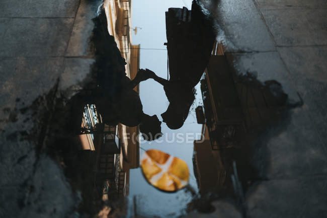 From above dark silhouette of romantic kissing couple reflecting in big puddle with autumn leaf in city road — Stock Photo