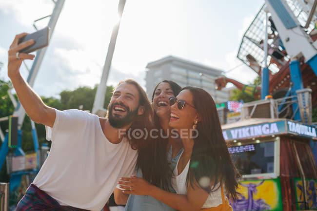 Веселые улыбающиеся загорелые люди фотографируют на смартфоне, стоя рядом с аттракционом на карнавале — стоковое фото