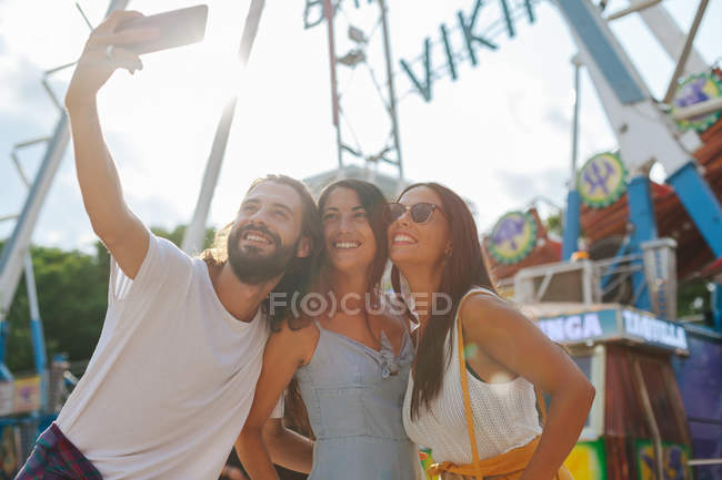 Allegro sorridente abbronzato persone scattare foto su smartphone mentre in piedi accanto all'attrazione al carnevale — Foto stock