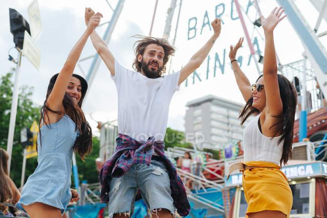 Энтузиазм случайных людей, прыгающих с поднятыми руками возле аттракциона на карнавале — стоковое фото