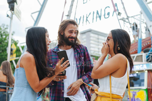 Cheerful smiling tanned people taking photo on smartphone while standing next to attraction at carnival — Stock Photo