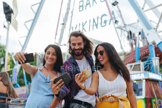 Cheerful smiling tanned people taking photo on smartphones while standing next to attraction at carnival — стокове фото