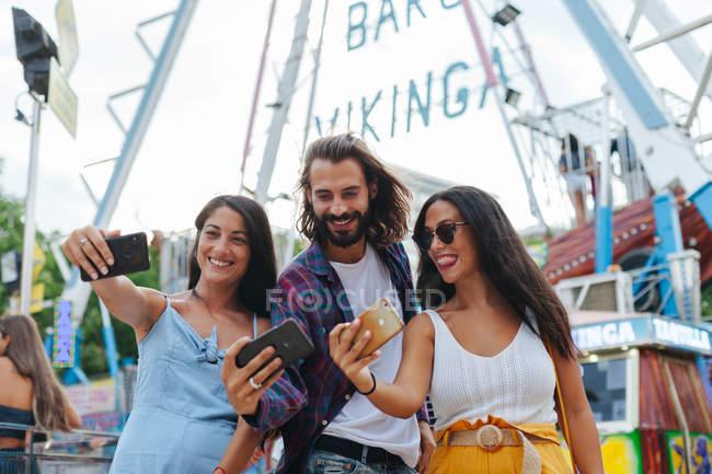 Веселих усмішок засмаглі люди фотографують смартфони, стоячи біля принади на карнавалі. — стокове фото