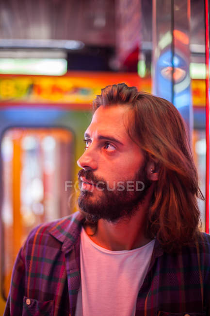 Smiling content casual man standing by mirror wall at carnival with multicoloured neon lights — стокове фото