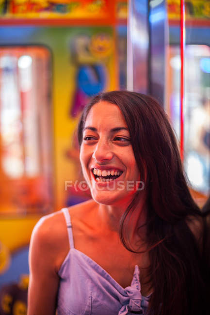 Side view of attractive delighted woman gazing at stand on carnival in red lights — стокове фото